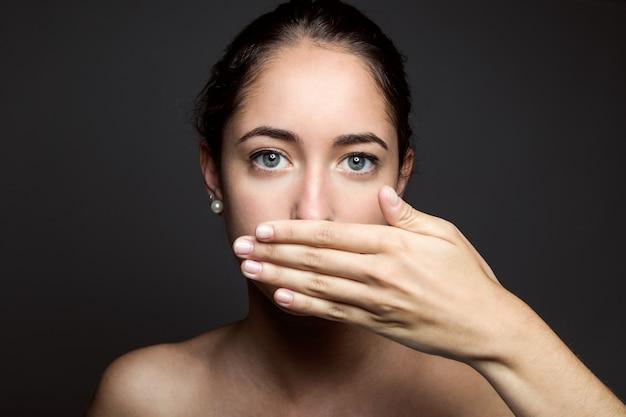 Hermosa mujer joven que cubre su boca con la mano. aislado.