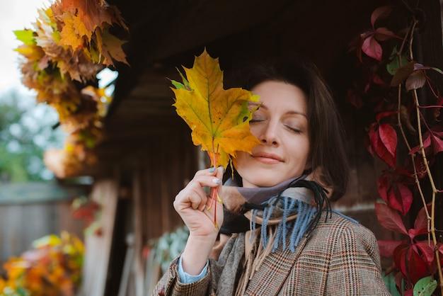 Hermosa mujer joven que cubre su rostro con una hoja amarilla de otoño, sonriendo contra el follaje enrojecido.