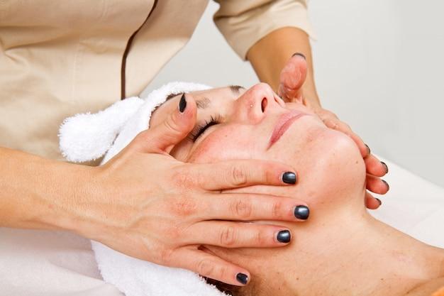 Hermosa mujer joven que recibe un masaje facial con los ojos cerrados en un centro de belleza