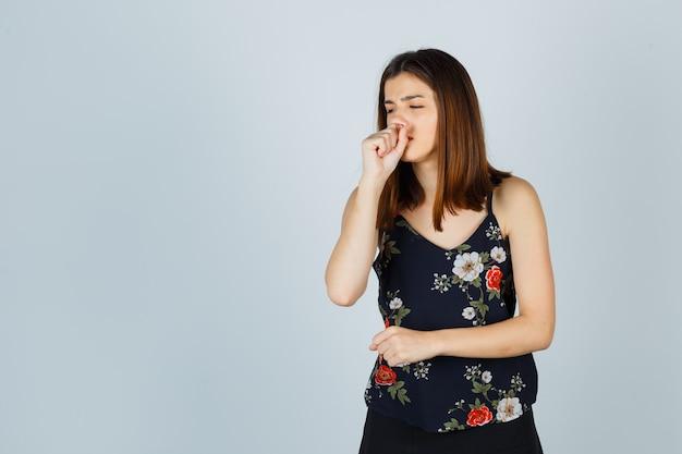 Hermosa mujer joven que sufre de tos en blusa, falda y aspecto enfermo