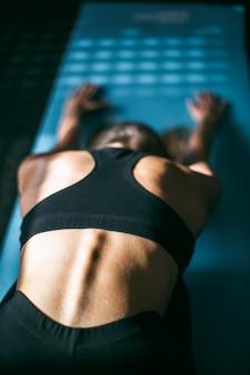 Hermosa mujer joven que trabaja en el gimnasio, haciendo ejercicio de yoga de curva hacia adelante en la alfombra azul