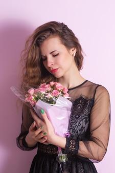 Hermosa mujer joven con un ramo de delicadas rosas rosadas
