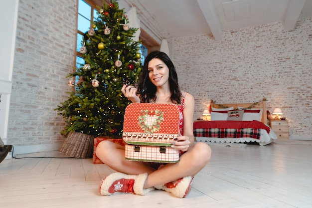 Hermosa mujer joven con regalos en el árbol de navidad
