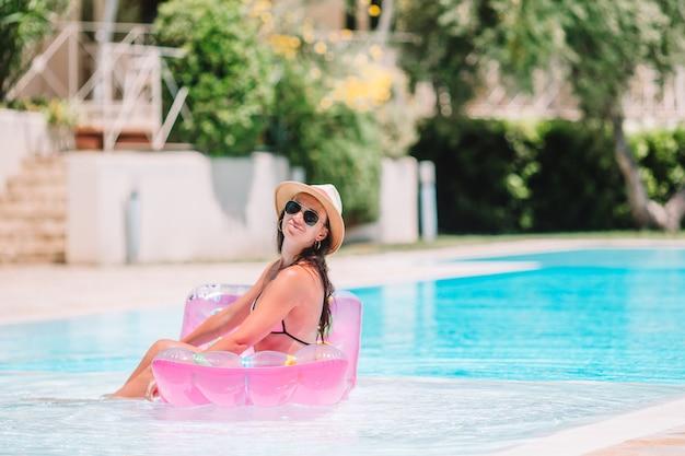 Hermosa mujer joven relajante en la piscina.