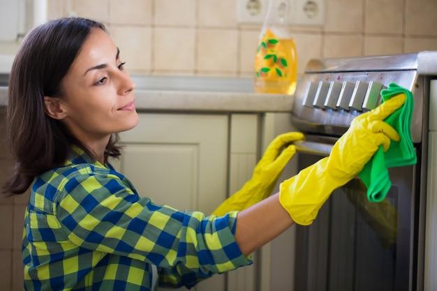 Hermosa mujer joven en ropa casual está limpiando la estufa eléctrica en la cocina mientras limpia su casa.