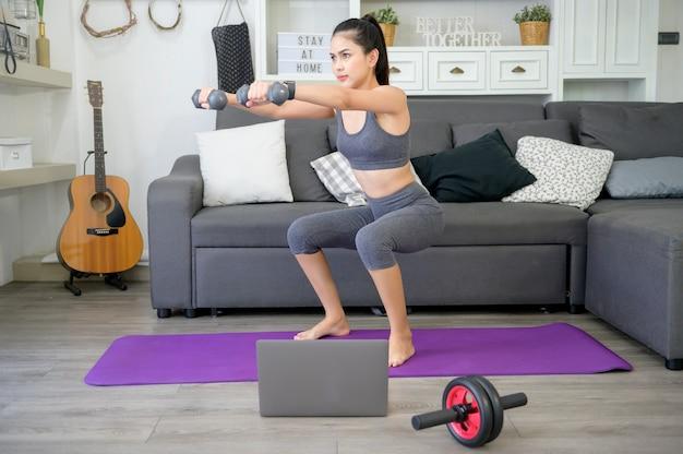 Hermosa mujer joven en ropa deportiva haciendo ejercicio con pesas en casa