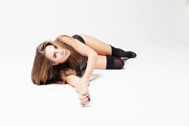 Hermosa mujer joven en ropa interior se sienta en el piso