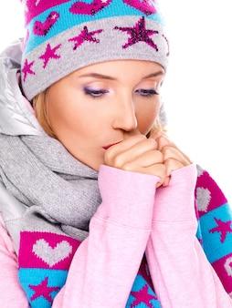 Hermosa mujer joven en ropa de invierno calentándose las manos