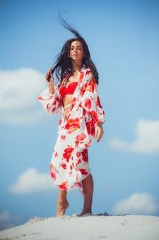 Hermosa mujer joven en ropa de playa camina sobre la arena