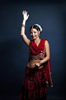 Hermosa mujer joven en ropa tradicional india bailando