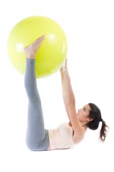 Hermosa mujer joven saludable haciendo ejercicio con balón