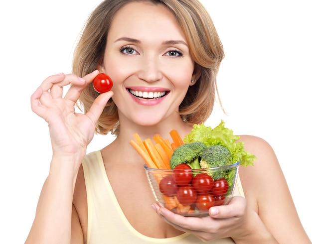 Hermosa mujer joven y sana con un plato de verduras - aislado en blanco.