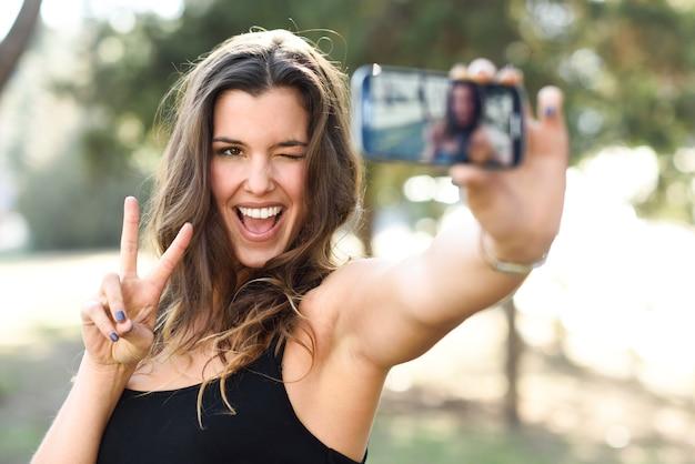 Hermosa mujer joven selfie en el parque
