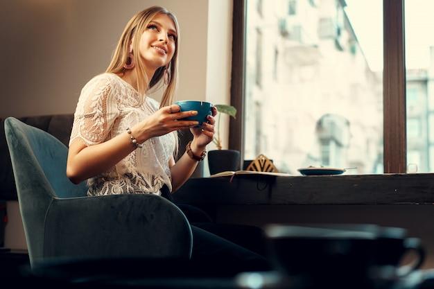 Hermosa mujer joven sentada en la cafetería disfrutando de su bebida