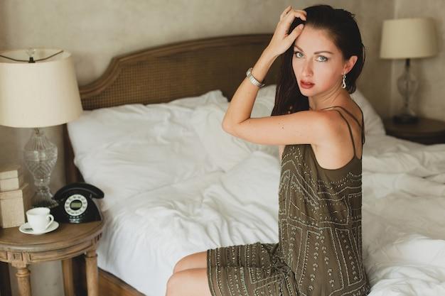 Hermosa mujer joven sentada en la cama en la habitación del hotel, elegante vestido de noche, coqueto, sexy, traje de moda, sábanas blancas