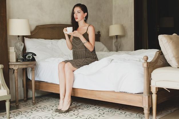Hermosa mujer joven sentada en la cama en el hotel, vestido elegante, humor sensual, tomando café, sosteniendo la taza