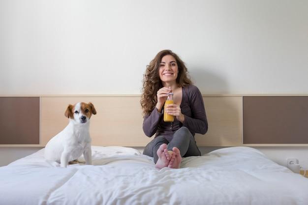 Hermosa mujer joven sentada en la cama con su pequeño perro lindo además.