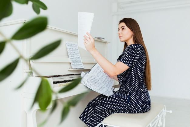 Hermosa mujer joven sentada cerca del piano mirando hoja musical