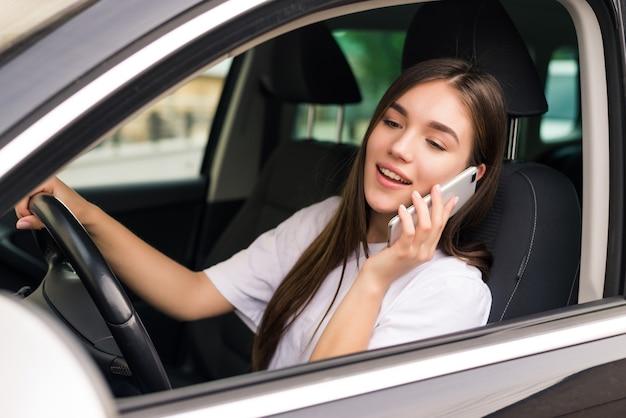 Hermosa mujer joven sentada en el coche con ordenador portátil y hablando por teléfono.