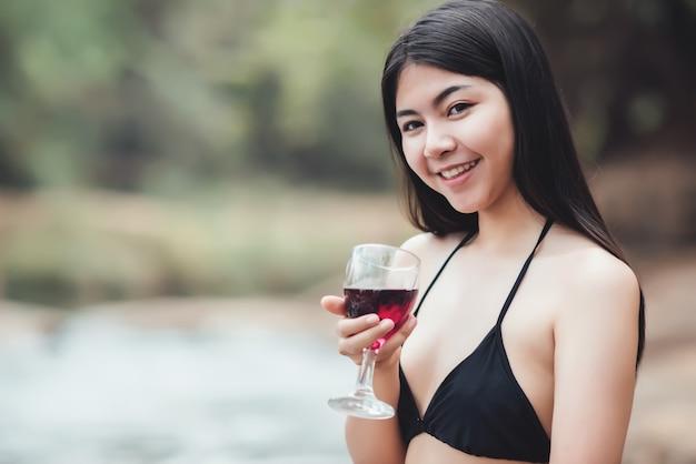 Hermosa mujer joven sentada en un cóctel al aire libre y mirando el río