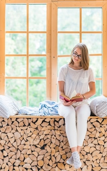 Hermosa mujer joven sentada delante de libro de lectura de la ventana