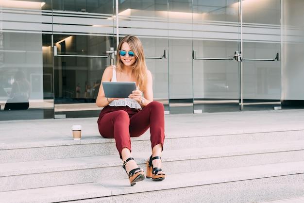 Hermosa mujer joven sentada en las escaleras de la tableta con gafas de sol