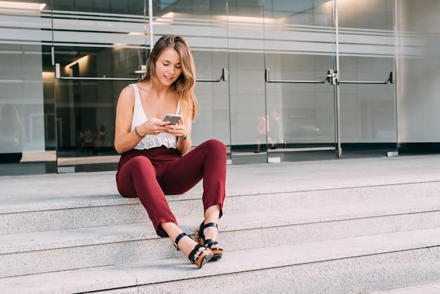 Hermosa mujer joven sentada en las escaleras en el teléfono móvil