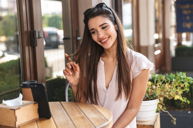 Hermosa mujer joven sentada en la mesa de café al aire libre