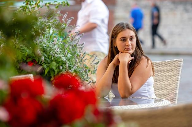 Hermosa mujer joven sentada en la mesa del café de la calle y esperando la reunión, flores desenfocadas en primer plano