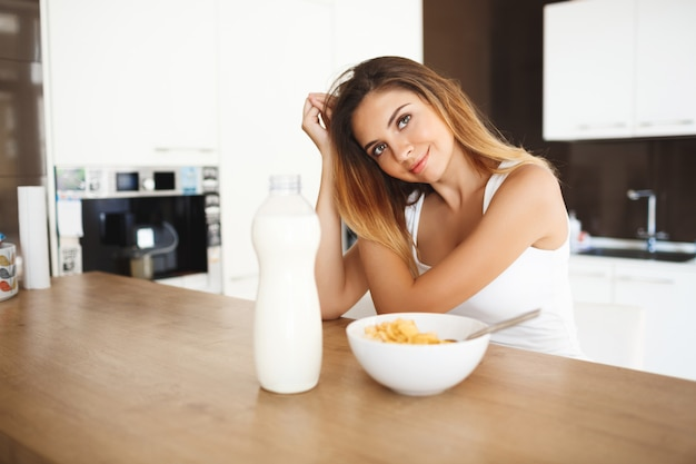 Hermosa mujer joven sentada en la mesa con desayuno listo sonriendo
