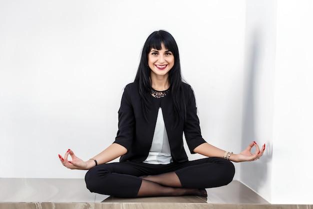 Hermosa mujer joven sentada en posición de loto en un piso de la oficina, sonriendo