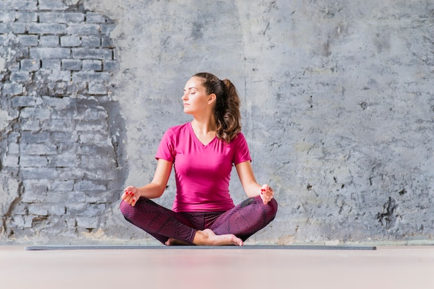 Hermosa mujer joven sentada en posición de yoga meditando