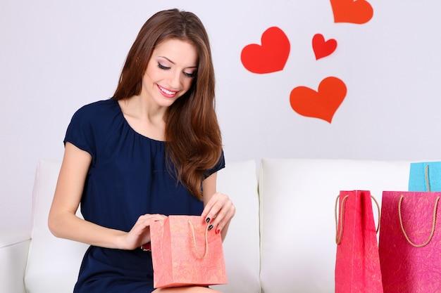 Hermosa mujer joven sentada en un sofá con bolsas de compras sobre fondo gris