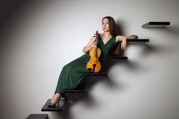 Hermosa mujer joven sentada con violín en las escaleras sobre fondo blanco.