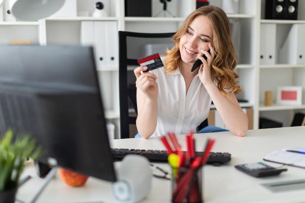 Hermosa mujer joven se sienta en la oficina, tiene una tarjeta bancaria y un teléfono en la mano.
