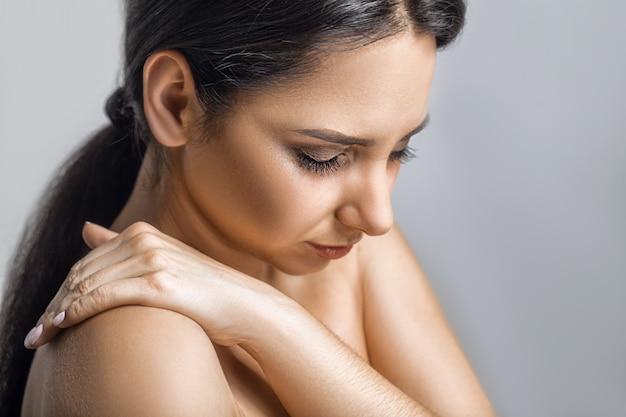 Hermosa mujer joven sintiendo dolor en el hombro