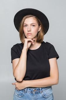Hermosa mujer joven en sombrero disquete negro posando aislado