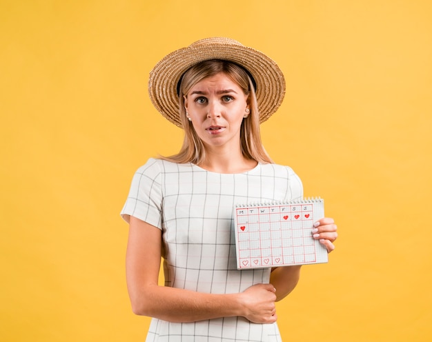 Hermosa mujer joven con sombrero con dolor de estómago