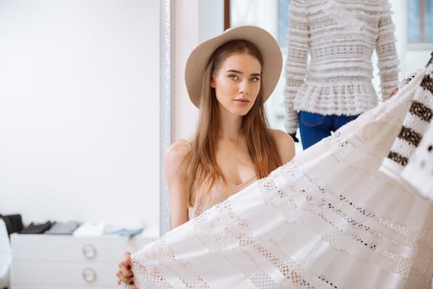 Hermosa mujer joven con sombrero eligiendo ropa en tienda de ropa