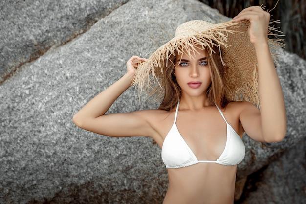 Hermosa mujer joven en un sombrero de paja en una de una playa rocosa