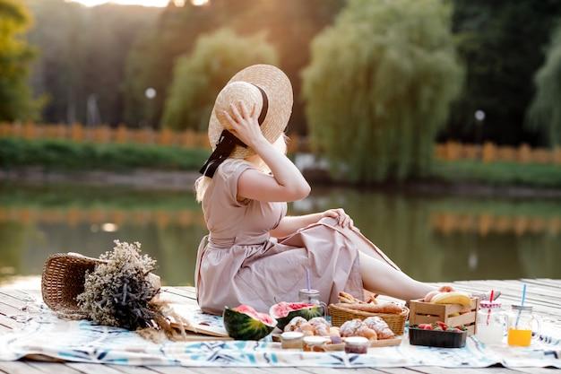 Hermosa mujer joven con sombrero de paja y vestido rosa tiene picnic cerca del lago en el bosque de verano. un mantel con una cesta de flores, sandía, bebidas de verano y cruasanes.