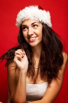 Hermosa mujer joven con sombrero de santa claus se está riendo. vertical. rojo .