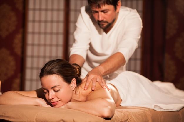 Hermosa mujer joven sonriendo con los ojos cerrados, recibiendo masaje de espalda en el centro de spa. masajista profesional dando masaje relajante a su cliente. hoteles, resorts, mimos