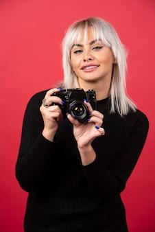Hermosa mujer joven sosteniendo una cámara mientras está de pie contra el fondo rojo. foto de alta calidad