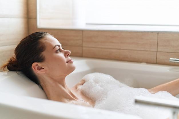 Hermosa mujer joven en su hermosa bañera blanca como la nieve descansa y se relaja, hermosa evidencia, bañera con espuma