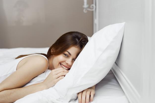 Hermosa mujer joven en su hermosa cama blanca como la nieve se relaja y se relaja, hermosa evidencia