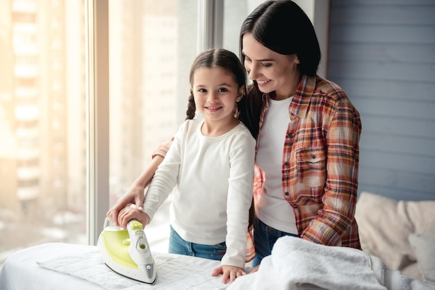 Hermosa mujer joven y su pequeña hija están sonriendo