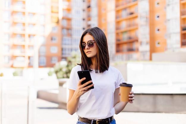 Hermosa mujer joven con su teléfono inteligente con una sonrisa mientras camina al aire libre