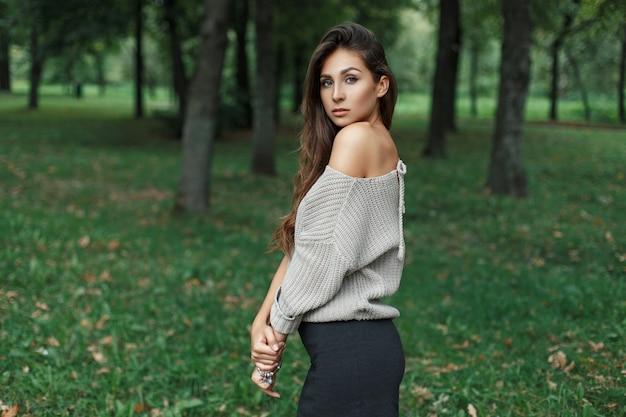 Hermosa mujer joven en suéter gris vintage posando en el parque