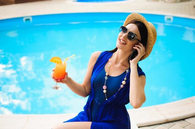 Hermosa mujer joven con teléfono junto a la piscina